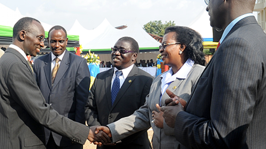 Chief Justice Sam Rugege (L) greets EALA Speaker Margaret Zziwa while looking on are EAC Secretary General Dr. Richard Sezibera (2 left) , East African Court of Justice President Harold Nsekela (2 right)   and Principal Judge Johnston Busingye at the inau