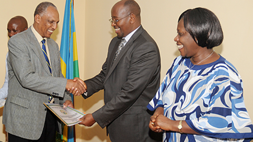 Demobilisation and Re-Integration commission Chairman Jean Sayinzoga (L) presents his performance contract document to Local Government Minister James Musoni on Wednesday as State Minister Alivera Mukabaramba looks on. The Sunday Times, John Mbanda.