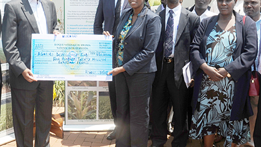 Finance Minister John Rwangombwa (L) receives a 420 Million franc cheque for Agaciro DF from Agriculture Minister Agnes Kalibata as other Ministry staff look on.  The Sunday Times/ John Mbanda