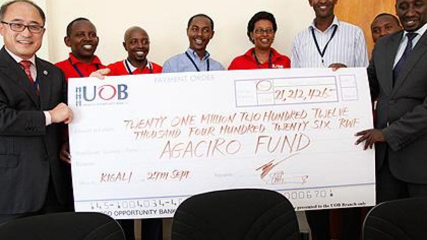 UOB's Jeffrey Lee (L) hands over the dummy cheque to Ronald Nkusi of the Ministry of Finance.  The Sunday Times / P. Mbabazi