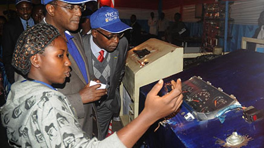 A female auto-mechanic student explains to Education Minister Vincent Biruta (2nd left) and State Minister Mathias Harebamungu how a petrol engine works, at the launch of the TVET Expo on Thursday.  The New Times / John Mbanda.