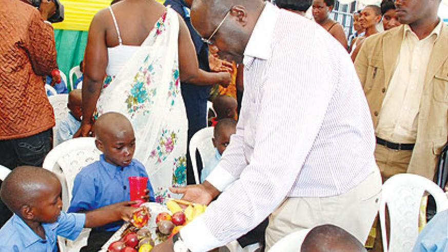 Premier Pierre Damien Habumuremyi feeds a child at the closing of the Family Campaign. The New Times / Courtesy.