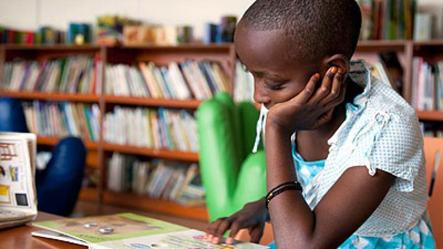 A child reading a textbook at Kigali Public Library. The New Times / T.Kisambira.