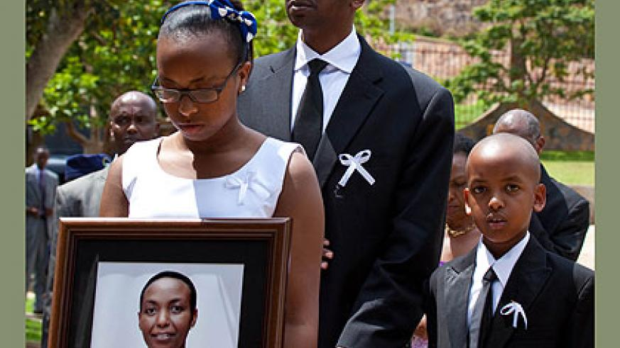 GONE TOO SOON: Husband to the late Aloisea Inyumba, Richard Masozera, with their children Nicole, 16, and Noah, 8, at the funeral yesterday. The New Times / Timothy Kisambira.
