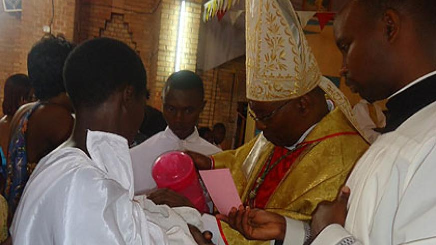 bishop phillipe rukamba baptises a child during the celebrations of chrismas at butare catholic diocese - Do Catholics Celebrate Christmas