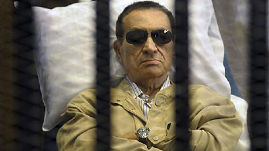 Egypt's ex-President Hosni Mubarak lays on a gurney inside a barred cage in the police academy courthouse in Cairo, Egypt.