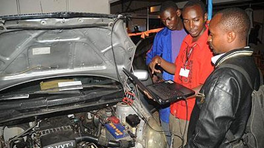 An exhibitor explains how to monitor an engine  using a computer during the recent TVET Expo. The New Times / File.
