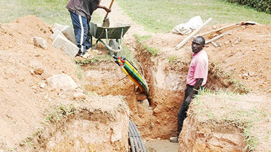 Workers lay Fibre Optic Cables in Kigali recently. A 2012 report says Internet access is still minimal across the country. The New Times/ File.