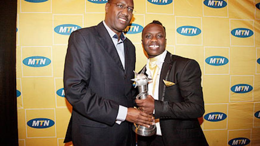 The Minister of Sports and Culture Protais Mitali (Left), poses for a photo with the winner of the 2011 Salax Awards, King James.  The New Times / File.