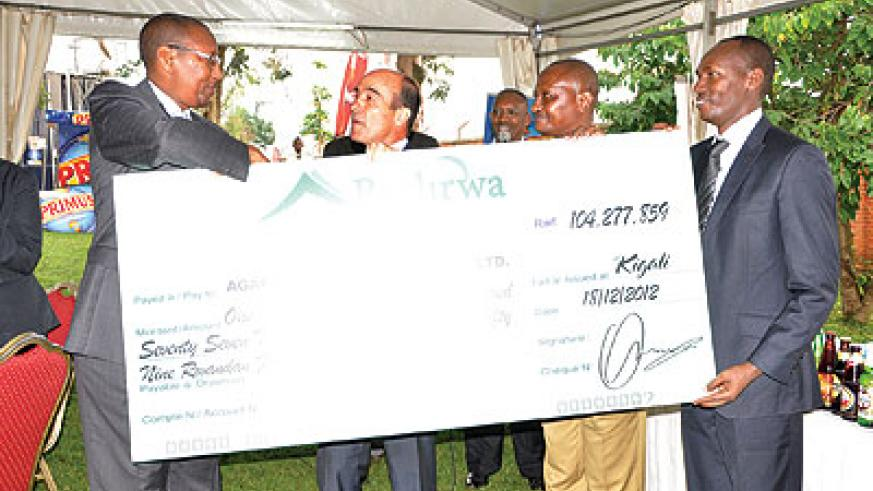 Finance minister Rwangombwa (left) receives the contribution dummy cheque from Bralirwa MD, Jonathan Hall (centre) on Wednesday. The New Times/Ben Gasore .