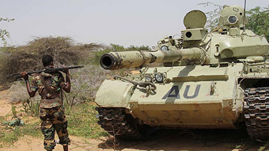 A Somali Transitional Federal Government soldier stands beside an AMISOM tank in the front lines of the battle against al-Shabaab. The Somali government has asked the UN to lift the ar....