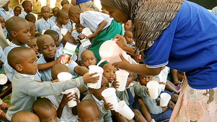 Children receive milk under the programme. The New Times/ File.