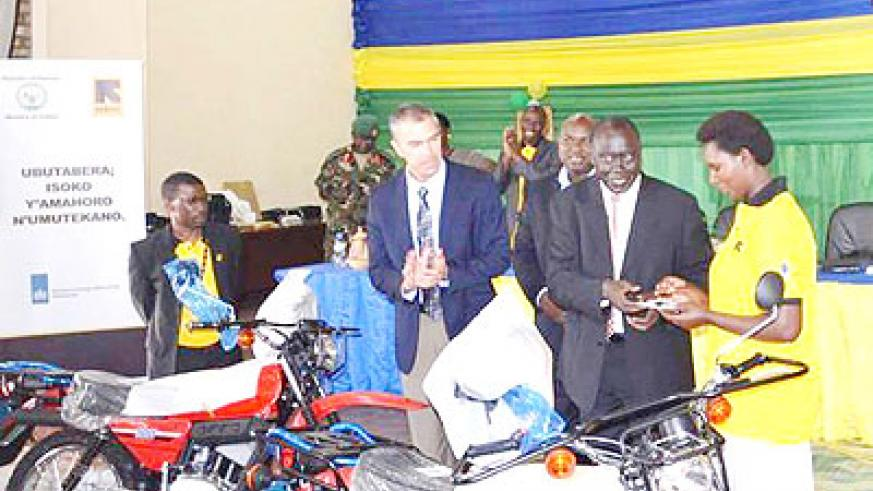 Karugarama (2ndR) hands over motorcycles keys to MAJ staff as Crothers looks on. The New Times/ S. Rwembeho
