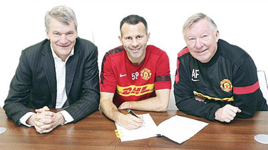Ryan Giggs puts pen to paper with manager Sir Alex Ferguson (right) and chief executive David Gill.  Net photo.