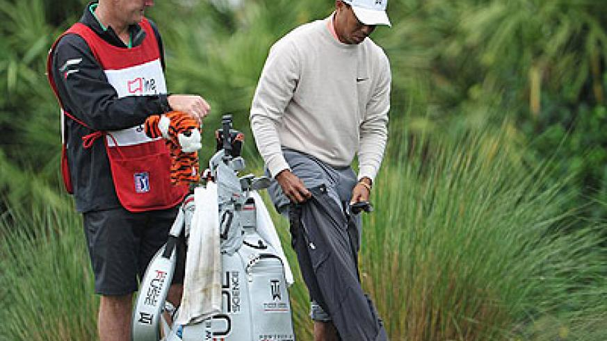 Tiger Woods hit a 200-yard shot out of a water hazard after finding his ball. Net photo.