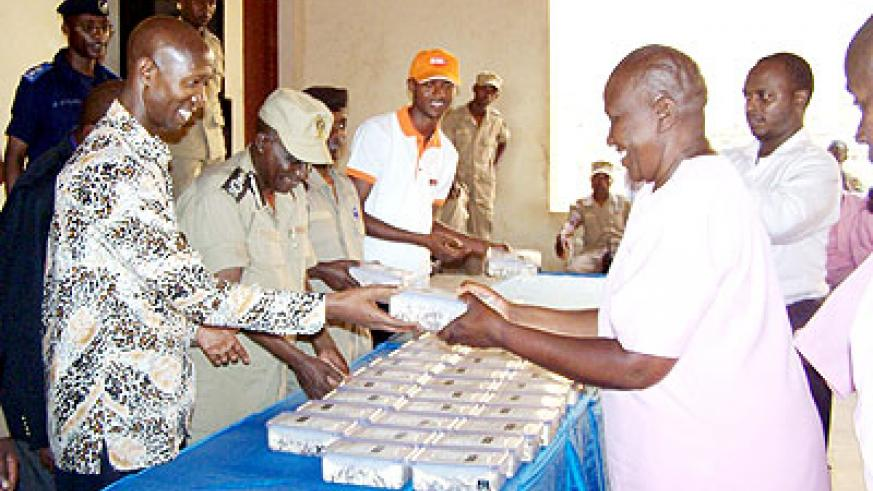 Harelimana (L) serves packed food to Huye Prison inmates in July last year. The New Times/ File.