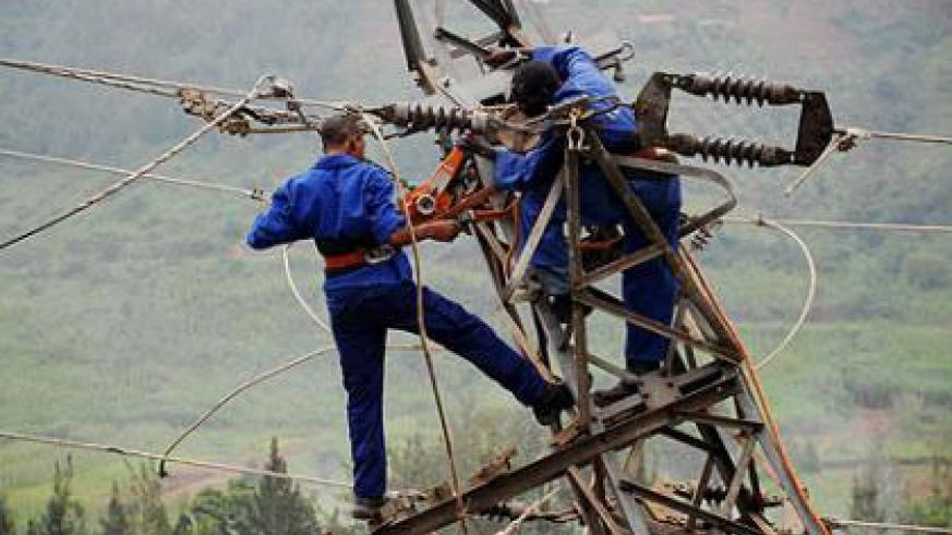 Energy Water and Sanitation Authority (EWSA) workers fix a power transmission line. The New Times / File.