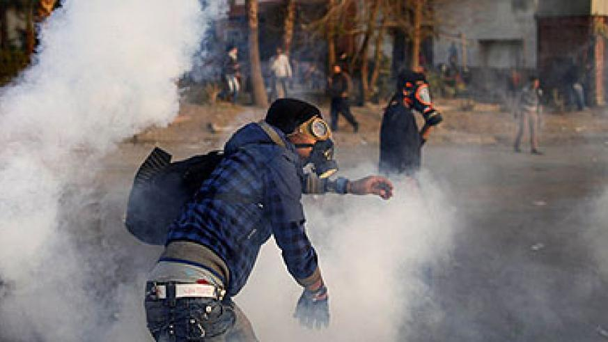 <p>An Egyptian protester throws back tear gas canisters during clashes with riot police near Tahrir Square in Cairo on March 9, 2013. A court verdict over deadly football violence spar....