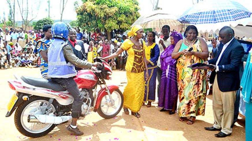 Mukasonga (2nd R) and AEE's Phanuel Sindayiheba (R) hand over a motorcycle to a beneficiary.  The New Times/  Laurent Kamana.