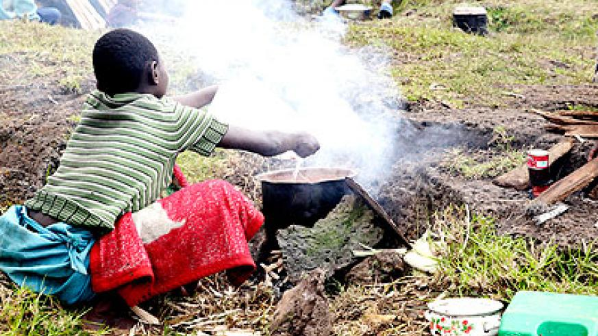 A Congolese refugee prepares food in a camp. The New Times/  File