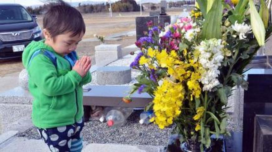 A little boy prays for his relatives killed in the 2011 disaster. Net photo.