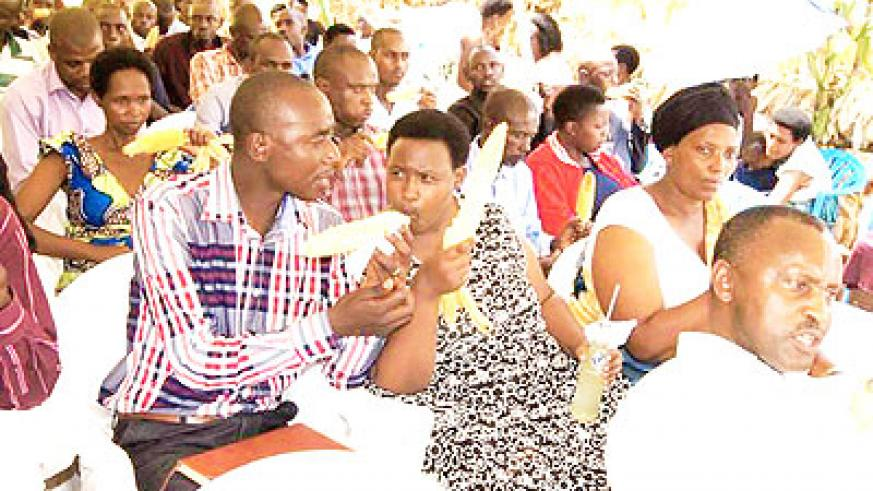 Farmers enjoy boiled maize during the function. The New Times/ Steven Rwembeho.