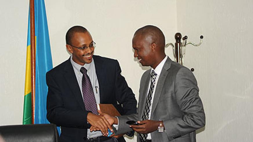 Karitanyi (left) shakes hands with Muyange after receiving tools of  office on Monday. The New Times/ Johm Mbanda