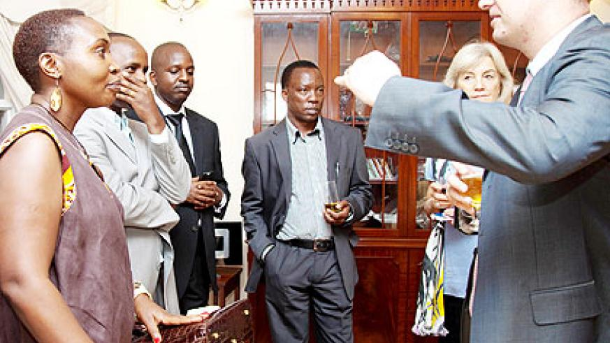 Llewellyn-Jones (R) talks to his guests during the function yesterday.  The New Times/ T. Kisambira.