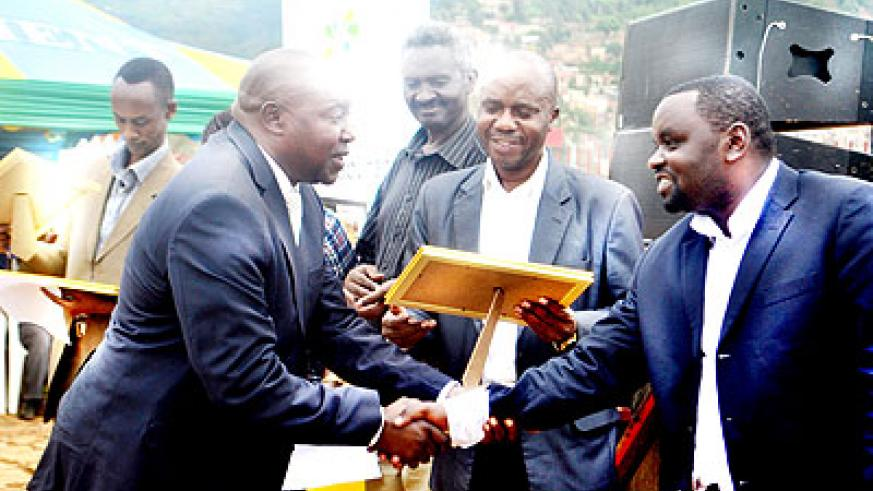Nzeyimana (R) congratulates one of the taxpayers rewarded yesterday.  The New Times/ Courtesy.