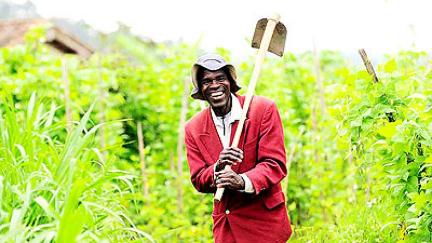 A farmer radiates with a smile after a day's labour. The Premier has called for hard work in the new season.  The New Times/ Timothy Kisambira.