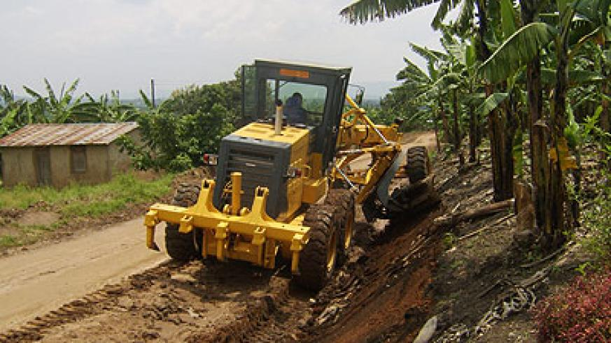 Grader opens a road in rural Uganda. AfDB is funding a road improvement project in the country. Net photo.