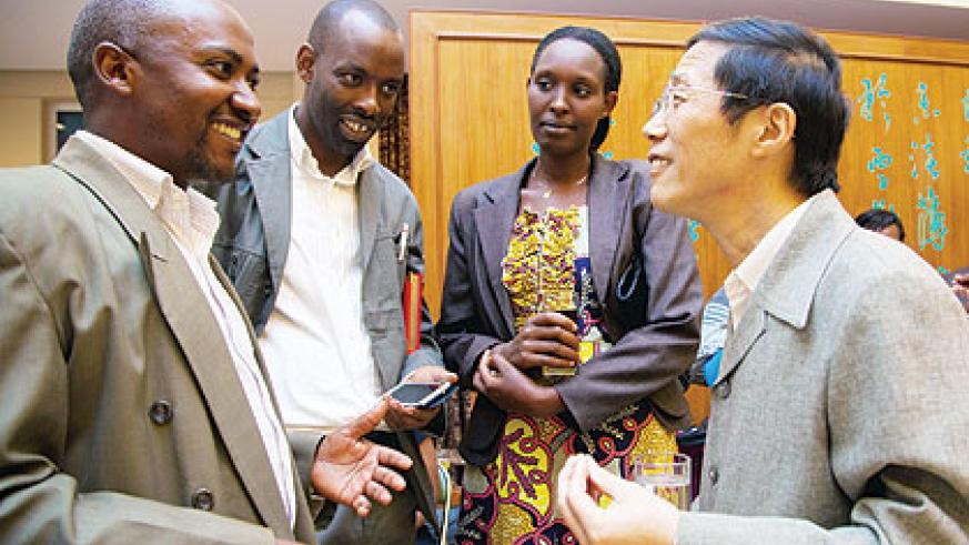 Zhan (R) interacts with some Rwandans who have benefited from Chinese government training. The New Times/ Timothy Kisambira.