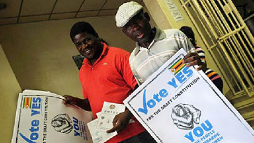 Men hold up posters calling on Zimbabweans to vote yes in the constitutional referendum. Net photo.
