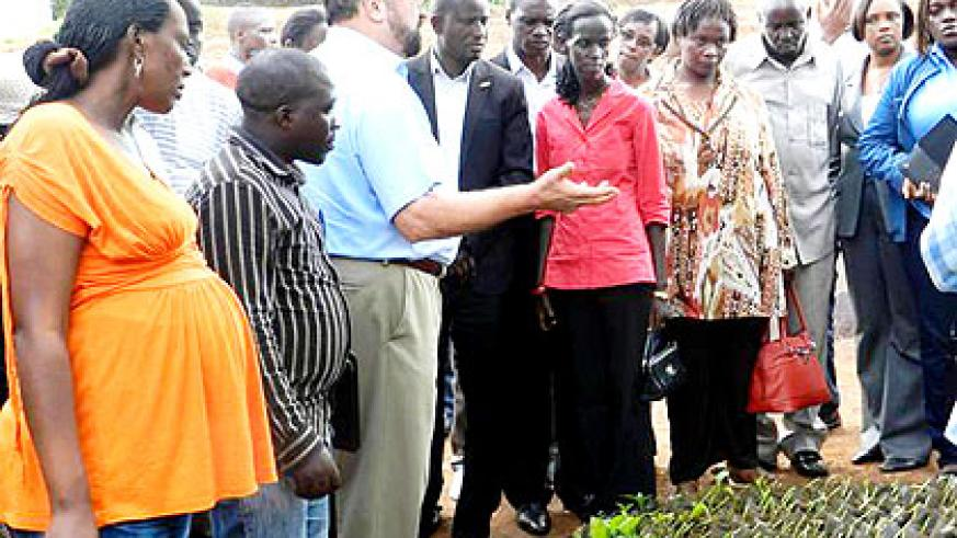 Jones explains to the touring leaders about his agro-forestry activities in Kigabiro sector.  The New Times/  Stephen Rwembeho.