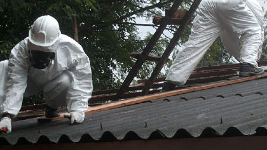 Experts remove asbestos sheets from a roof last year. Inset is a house with asbestos. The New Times/ File