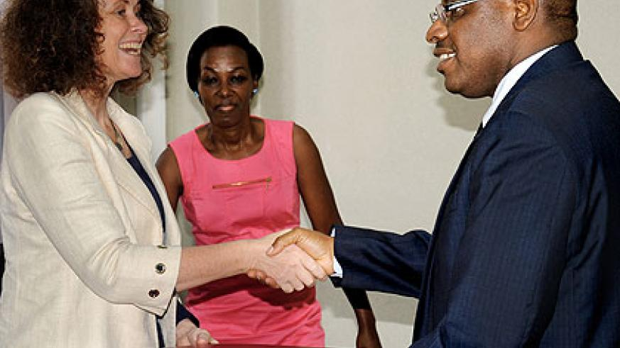Finance minister Claver Gatete (R) and World Bank Country Manager Carolyn Turk exchange files after signing the deal.The New Times/ J. Mbanda.