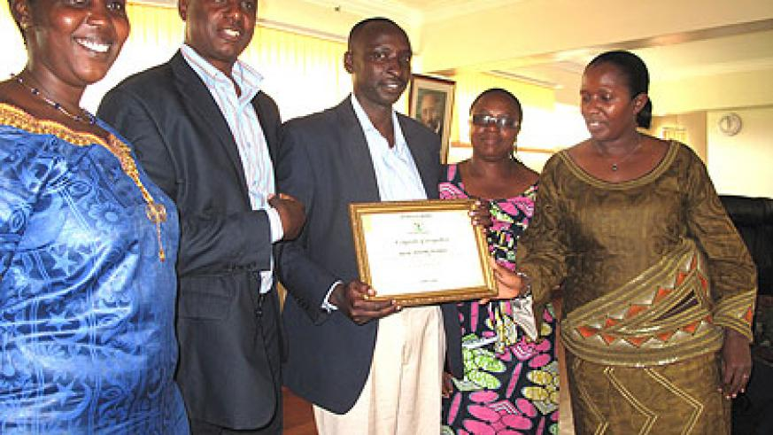 Governor Uwamariya (R) awards Byaruhanga certificate of recognition. The New Times/ Stephen Rwembeho.