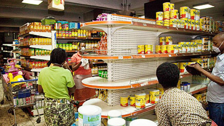 Simba Supermarket staff re-organise stalls after the fire outbreak yesterday. The New Times/ Timothy Kisambira.