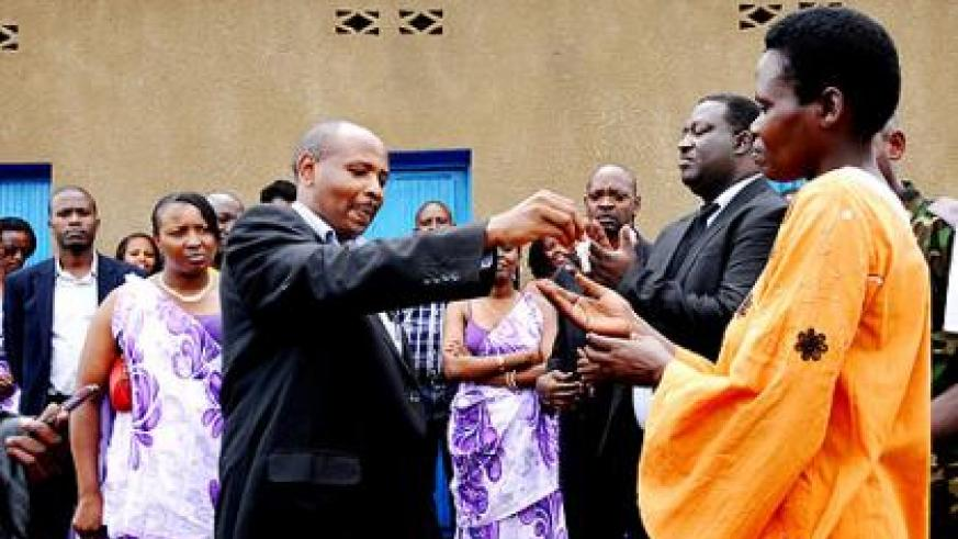 Rusagara hands over a house key to Jacqueline Kayitesi, a beneficiary.  The New Times/  Laurent Kamana.