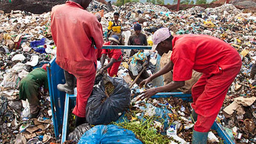 Waste collectors go about their business without protective gear. Most are at risk of  contacting life threatening diseases.  The New Times/Timothy Kisambira.