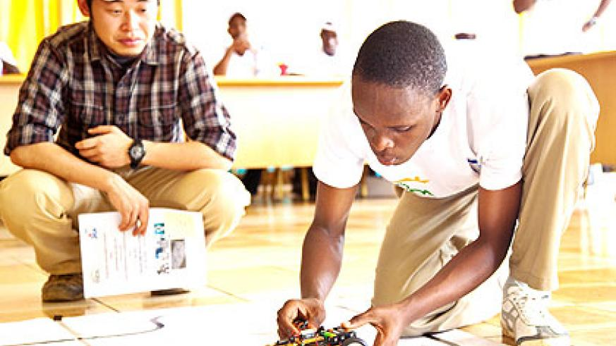 Joel Manishimwe (R) prepares his robot during the innovation contest yesterday. The New Times/  Timothy Kisambira.