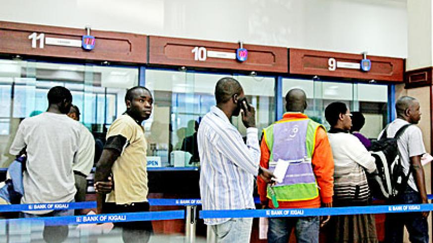 Clients queue in a city bank. A new project by MFIs could see many children learn savings culture at tender age.  The New Times/ File.