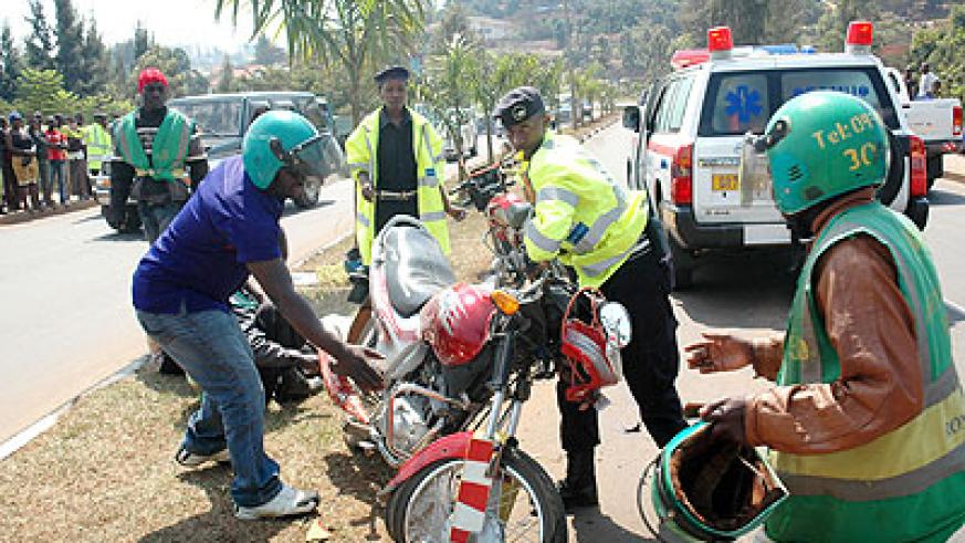 Traffic Police officers help a taxi-moto accident victim off the road recently. The New Times/ T. Kisambira.