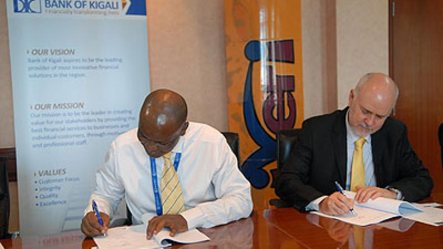 Naibo (left) and Coetzee sign the deal for e-commerce gateway at Bank of  Kigali headquarters yesterday.  The New Times/Courtesy photo..