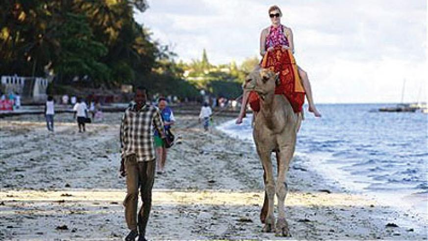 A tourist rides on a camel's back at the Jomo Kenyatta public beach in Kenya's coastal city of Mombasa. Kenya's tourism industry may be a swift winner from the election of Uhuru ....