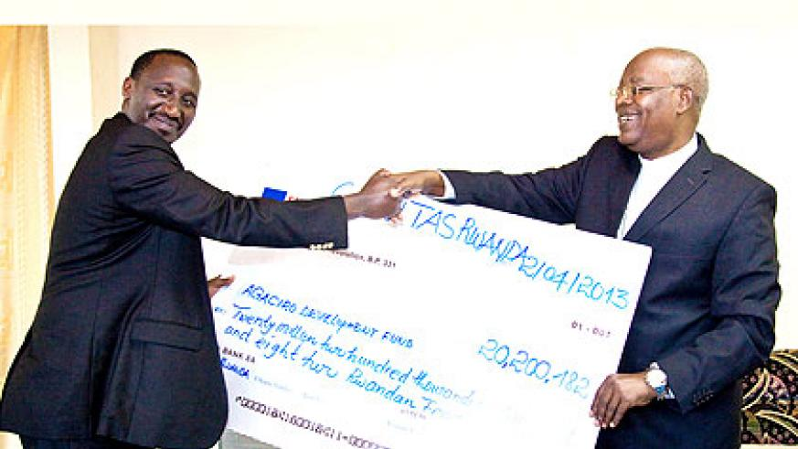Caritas-Rwanda's Thaddée Ntihinyurwa (R), also the archbishop of Kigali Diocese, hands a dummy cheque to Ronald Nkusi, the director of External Finance Unit at the Ministry of Finan....