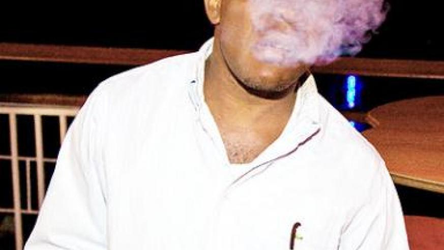 A man is engulfed in cigarette fumes in a public place. The New Times/ Timothy Kisambira.