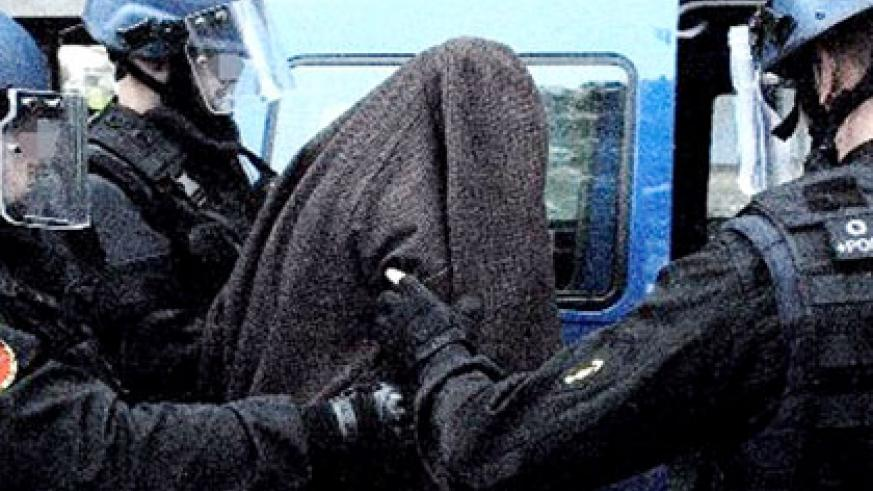Barahira (hooded) is led into a police van in Toulouse. Net photo.