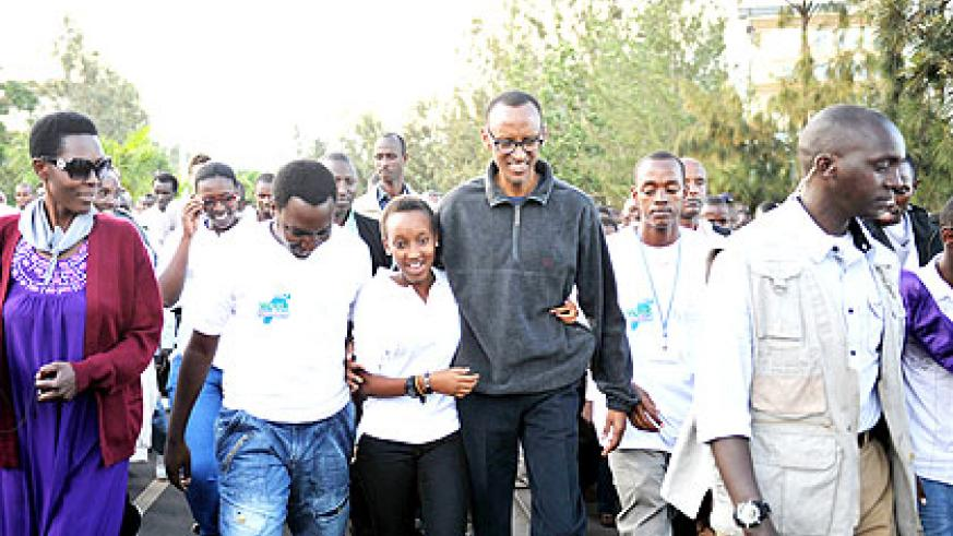President Kagame (in dark-blue blazer) holds a youth during the Walk To Remember in Kigali yesterday.   The New Times/ Village Urugwiro.