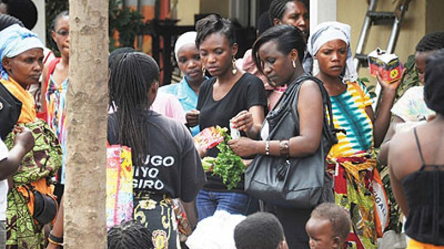 Women buy greens from a street vendor. Traders in Biryogo are complaining about street vendors 'taking' their clients. The New Times / Timothy Kisambira